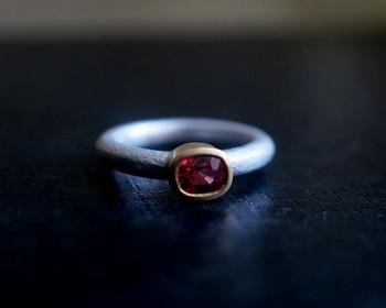 ■Kuraishi Takamichi/灯りの指環 「茜音 (スピネル)」  赤、ピンク、紫、青、黒、緑といった多彩な色を持つ「スピネル」。ルビーやサファイアとの見分けが難しいといわれる天然石です。スピネルは生命力のエネルギーを高め、目標を達成する力をもたらします。  K18イエローゴールドとシルバーを使ったスピネルのリングは、時を経た渋みを感じさせてくれます。
