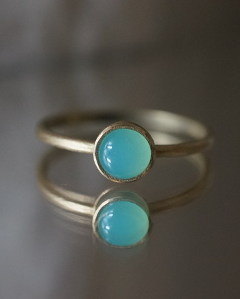 ■Kuraishi Takamichi/K18YG×ブルーオパール 「青の実」  古代ローマでは神の石ともいわれたブルーオパール。幸福と希望を導く石として愛されてきました。カボションカットで石の持つ本来の輝きがよく表れています。憂いを帯びたようなやわらかなブルーがとても美しいですね。