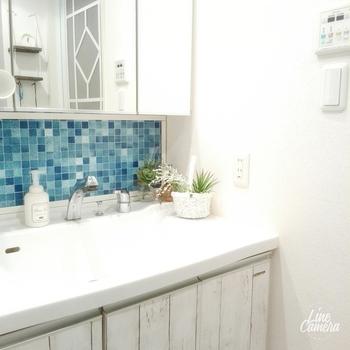 初心者さんは、洗面所の一部など狭い範囲から試してみるのがおすすめです。こちらは、洗面台の下に、ブルーのモザイクタイル風のリメイクシートを貼ったアレンジ。白い壁とのコントラストが涼しげで、清潔感もアップしてくれます。