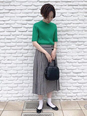 目を惹くグリーンのリブトップスにギンガムチェックのスカートを合わせたキュートなスタイリング。足元には白の靴下とバレエシューズを合わせて、レトロっぽさを出すとGOOD。小物を黒でまとめることでキュートなスタイリングも甘くなりすぎず◎。