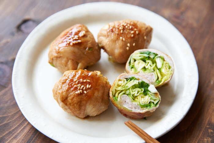 肉巻きレシピは野菜を一緒にいただけるので、野菜嫌いの子供でも美味しくいただけて、お弁当に入れても絵になります。こちらは千切りキャベツがたっぷり入った肉巻き。肉を十字に置いて、キャベツを巻くことで、コロコロと可愛らしい見た目に仕上がります。