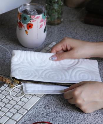 サークル状のステッチがおしゃれな、マスクもしっかり入る「フラットポーチ」。白いベロアで季節を問わず使用できます。ストラップ付きで、クラッチバッグのように持つこともできて使い道いろいろ。