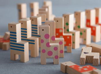 木のおもちゃブランド「PaPaCo YOSHINO」が奈良県吉野の森の端材や間伐材を使用して作ったおもちゃ。ひのき材のキリンさんに、さまざまなカラフルな模様が描かれたドミノです。