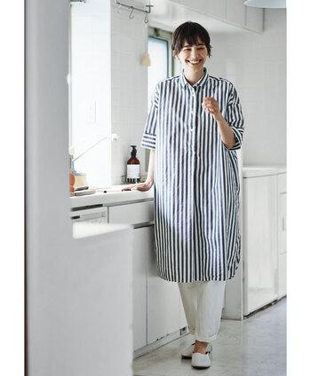 ストライプ柄のロングシャツに、白のズボンを合わせた爽やかな夏コーデ。足元も白で揃えて、女性らしい着こなしにまとめています。羽織りとしても使えるロングシャツは、あえて前を閉めてワンピース風に着こなしても素敵です。