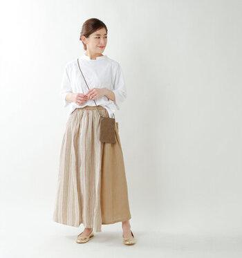 マルチストライプ柄のベージュスカートに、白トップスを合わせたナチュラルなコーディネート。トップスをゆるくボトムスにタックインして、きっちり感を抑えた着こなしにまとめています。足元はゴールドのパンプスで、スカートと色味を合わせつつワンアクセントになるようなスタイリングに。