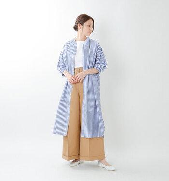 青と白のストライプ柄ワンピースを、羽織りとして活用したコーディネートです。白のシンプルなトップスを、ベージュのワイドパンツにタックイン。ボトムスにボリューム感のある着こなしを、ストライプ柄ワンピースでキュッとコンパクトに見せているのがポイントです。足元は白のパンプスで、女性らしさをアピール。