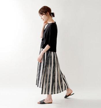 太めなストライプデザインの黒×ベージュスカートに、黒トップスを合わせたクールなコーディネートです。足元のサンダルも黒で色を合わせて、全体を統一感のあるスタイリングにまとめています。トップスはあえてタックインせず、リラックス感のある着こなしに。