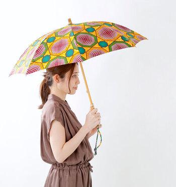 シンプルなTシャツコーデには、大胆な色柄の日傘でアクセントを。柄はバンブー素材で、海コーデにも合うナチュラルな雰囲気です。
