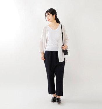 白のベーシックなタンクトップに、透け感のあるシャツを羽織ったシンプルスタイル。黒のパンツに同色のショルダーバッグとシューズで、全体をモノトーンでクールにまとめています。