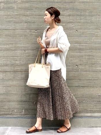 ベージュのタンクトップに、白シャツをゆるく羽織ったコーディネート。ボトムスはブラウン系の総柄プリーツスカートで、女性らしさをしっかりと演出できるスタイリングです。スカートと色味を合わせたクリアサンダルで、こなれ感たっぷりなフェミニンコーデの完成です。