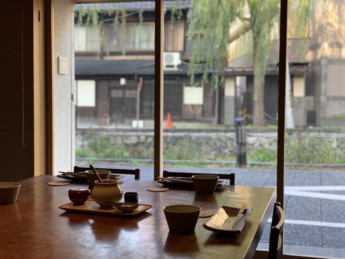 おばんざいとは、京都の家庭で古くから作られてきたお惣菜のこと。京野菜を中心に薄味で作られているので、ヘルシーなのも嬉しい京都グルメです。  そんなおばんざいを朝からいただけるのが、白川のほとりに立つ「丹」。大きな窓からは、川沿いに植えられた柳や京都の街並みが眺められます。
