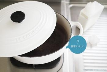 使い込んで真っ黒になった鍋の底。お鍋に水と小さじ2〜3の重曹を入れ、弱火で10分ほど沸騰させます。お湯の温度が下がったら、中性洗剤を使用しスポンジで洗います。