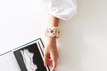 籐を素材に用いた新鮮な印象のバングルは、籐やニットを使って、アクセサリーや小物を製作している「L'Effrontée(レフロンテ)」さんの作品です。籐ならではのしなやかで強くて軽い特性を活かし、丁寧に編み込まれています。開口部や留め具などがないクローズドタイプのバングルですが、手をすぼめるように通して自分のサイズにギュッと縮めるだけで簡単に装着可能です。