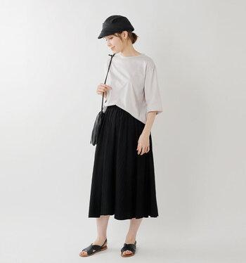 シンプルな黒のミモレ丈スカートに、ベージュのTシャツをゆるくタックインしたカジュアルコーデ。サンダルやバッグ、キャップの色を黒で統一して、ラフながらも大人っぽさをしっかりアピールできる着こなしにまとめています。