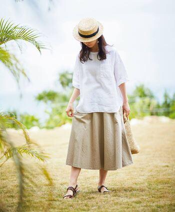 ベージュのミモレ丈フレアスカートに、白のトップスを合わせたベーシックなコーディネート。季節感のあるナチュラル素材のバッグとハットが、夏らしさをグッと高めてくれます。大人のデイリーコーデにも、ぴったりな着こなしですね。