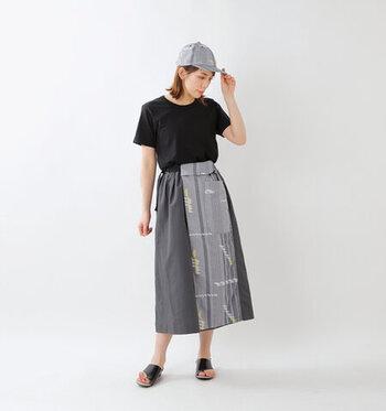 オリジナルジャガード生地とダークトーンの無地布を合わせた、ミモレ丈の柄スカート。主張の強いボトムスなので、トップスはシンプルな黒Tシャツをタックインしてスッキリとまとめています。フェミニンスタイルにぴったりな個性派ボトムスですが、あえてキャップやサンダルで大人の遊び心たっぷりな着こなしに。