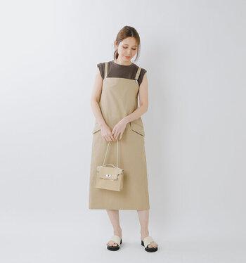 ミモレ丈のサロペットスカートに、ブラウンのフレンチスリーブトップスを合わせたコーディネート。サンダルやバッグもベージュ系のカラーで揃えて、統一感のあるスタイリングにまとめています。二の腕が気になる場合は、肩からシャツやカーディガンを羽織っても◎