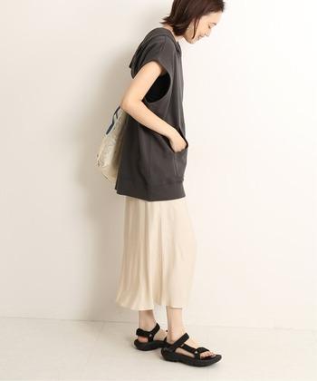 マーメイドデザインが女性らしい印象の、アイボリーのミモレ丈スカート。フェミニンスタイルにぴったりな一枚ですが、あえてフード付きトップスやスポサンを合わせて、デイリーコーデに取り入れやすいカジュアルコーデに仕上げているのがポイントです。