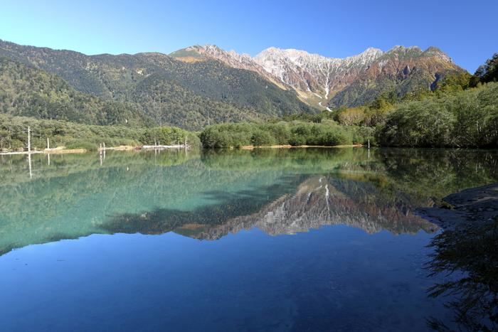 国の特別名勝・特別天然記念物に指定されている上高地の中でも、大正池では、特に素晴らしい景色を臨むことができます。波一つない静かな水面が、冠雪した穂高岳連邦の岩肌を鏡のように映し、眼前に広がる眺望は、一枚の絵画のようです。