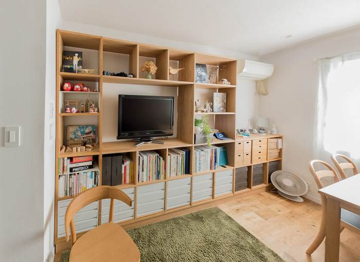 本好きなら、壁一面の本棚に一度は憧れるのではないでしょうか。このお部屋では、無印のシェルフを壁際にぴったり設置して、テレビ台、本棚、オープン収納などのスペースに。作りつけの壁面収納のように収まりがいいので、たくさんの本もすっきりして見えます。