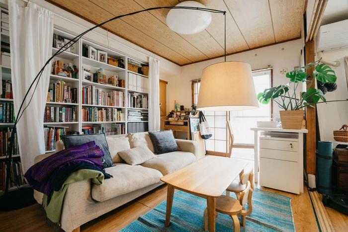 ソファの後ろに大きな本棚を置いて、家族のくつろぎスペースに。手前にはカーテンが取り付けられているので、お気に入りの本の日焼けが気になったり、来客があるときなどには隠すこともできます。こちらで使われているIKEAの本棚「BILLY」は、棚板の高さも調整できるので、本やレコードなどをたっぷり収納したい人に人気のアイテム。