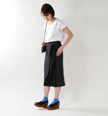 ひざ下丈のタイトスカートは、シンプルなトップスをinして。コーデのポイントは青いソックスとサンダル。シンプルコーデほど、足元に遊びを入れるとよりお洒落に見えますよ。
