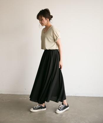 黒のフレアスカートは履くだけでシックに見える魔法のボトム。だからこそトップスやスニーカーで力を抜いて、リラックス感を演出しましょう。