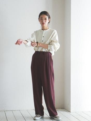 布の流れるような落ち感がきれいなパンツをコーデの主役に。色はブラウンだけど、切り替えに入っている2本のラインはパープルで、とてもおしゃれ。シンプルな白シャツをインして、ミニマルにまとめるとより印象的です。