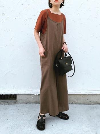ブラウンのサロペットに、トーン違いのブラウントップスを合わせたコーディネート。バッグとシューズを黒で統一して、フェミニンな印象になりやすいサロペットをクールに着こなしています。
