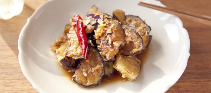 """上でご紹介したものと同じく""""なすの焼き浸し""""ではありますが、こちらの「香味野菜が香るなすの焼き浸し」は、フライパンで乱切りにしたナスを炒めて、あとは合わせ調味料と一緒に、味をなじむように炒めてつくります。  合わせ調味料は、ごま油、赤唐辛子、にんにく、しょうがなど。長ねぎも加わって、美味しいですよ。中華の副菜としても活躍しそうです。"""