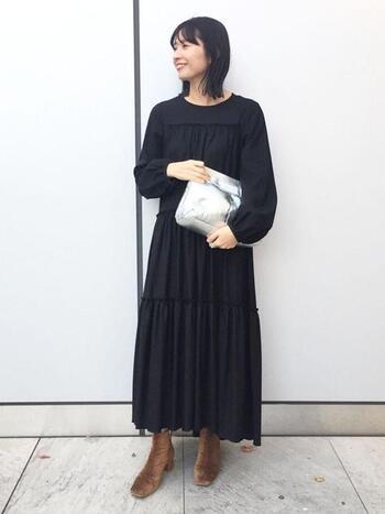シンプルながらも、ティアードデザインが女性らしいブラックワンピース。重く&地味になりがちな丈感ですが、シルバーのバッグで抜け感と華やかさを出しています。