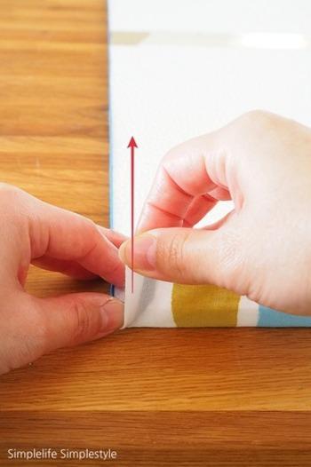 手ぬぐいを置いたら、両面テープを剥がして側面に貼り付けていきます。ポイントはしっかりと生地を引っ張ってしわやたるみを作らないことです。角はきちんと折って、余った生地の処理をしましょう。