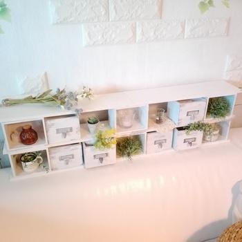 ダイソーのウッドボックスと引き出しを使った飾り棚収納。水性ペイントで板全体を白に塗り、引き出しの金具にはアクリル絵の具を使って軽くサビ感をつけるとシンプルすぎないオシャレな仕上がりに。白やベージュ系のペイントはナチュラル感が出やすいのでおすすめです。