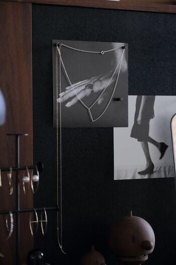 コルクボードに使うピンに、ネックレスをかけるアイデア。写真を一緒に飾る一工夫で、アートのようなおしゃれな雰囲気を演出しています。