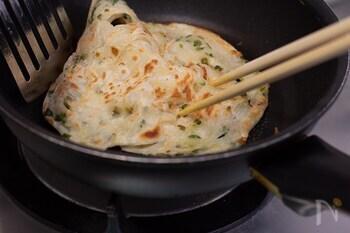 フライパンにごま油を熱して焼きます。火が通ったら、空気を含ませるようにフライ返しと菜箸で生地の両端を押して焼き上げてください。ふんわりと仕上がるポイントになります。 完成したら、食べやすい大きさに切って出来上がりです。