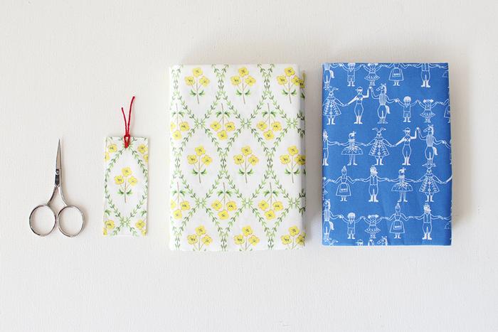 定規で本の大きさを測ったら、あとは2か所縫うだけの簡単なブックカバー。白地に黄色のお花のデザインが夏らしい雰囲気。布があまったら、一緒にしおりも作ってみましょう!