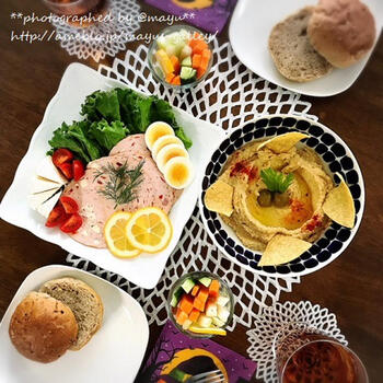 バンズや野菜、ゆでたまご、ハムなどサンドイッチの具に、そのままフムスをつけられるチップスや野菜スティックも用意して。彩りよくプレートに並べれば、ランチパーティーに映えるテーブルの出来上がり!