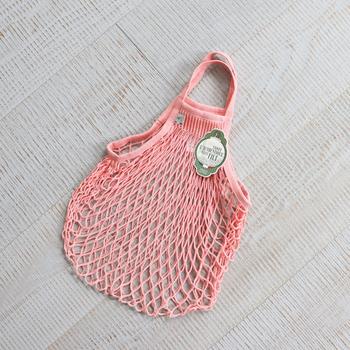 カジュアルなネットバッグに肌馴染みピンクを取り入れることで、シンプルなコーデもぐっと華やかになります。ピンクはあまり使わない人も、気負わず持てる小物から取り入れてみて。