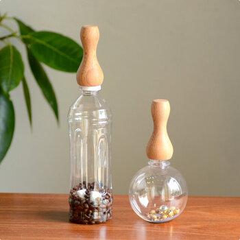 木製のグリップと丸い器がセットになっているおもちゃ。赤ちゃんがお気に入りのペットボトルなどに装着して、オリジナルのおもちゃを作ることもできるアイテムです。