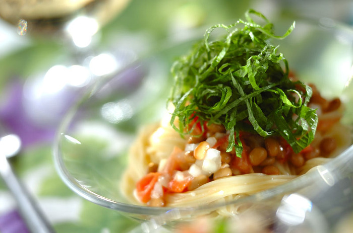 納豆は洋風レシピも人気です。暑い季節は、パスタも冷たいカッペリーニを使って。納豆に、トマトと塩、ニンニクなどを加えて作る調味料で和えて彩りよく仕上げています。たっぷり大葉をトッピングして爽やかに召し上がれ♪
