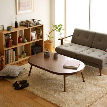 楕円形の折りたたみテーブル「CORONA」。ウォールナットの木目が美しく、ほっと一息つける優しさのある空間を作れますね。 幅120cmサイズは二人掛けのソファとも相性抜群。  スリムな印象ですが実はこたつ機能が付いているので、冬場もしっかり頼れますよ◎