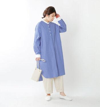 ストライプ柄の長袖シャツワンピースに、白ボトムスを合わせたスタイリングです。バッグやシューズなどの小物も白で揃えて、爽やかなキレイめコーデにまとめています。