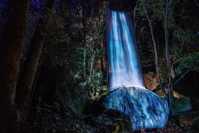 実際にある巨石に光の滝が降り注ぐアート。巨石を仮想の三次元空間に再現し、巨石の形によって変わる水の動きをシミュレーションして描かれたもの。水の粒子の連続体で表現したという繊細な水はまるで本物のよう。サーッと静かに流れ落ちる滝は神聖な雰囲気に満ちています。