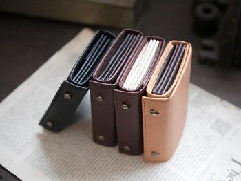小さな本のようなデザインがキュートなお財布。折り重ねた中身を一枚の革でぐるっと巻き留めたユニークな構造になっています。