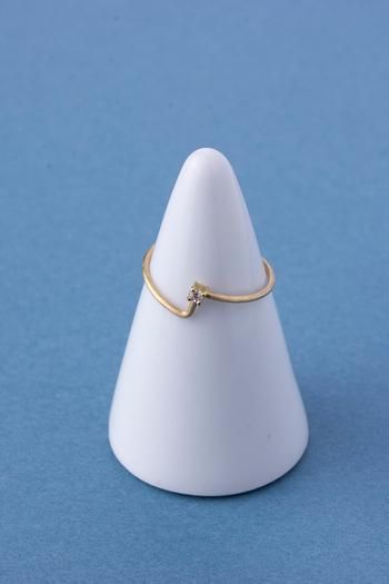 ユニークな形のリングにちょこんとダイヤをのせたジュエリー。遊び心がありつつ、品のあるデザインにまとまっています。