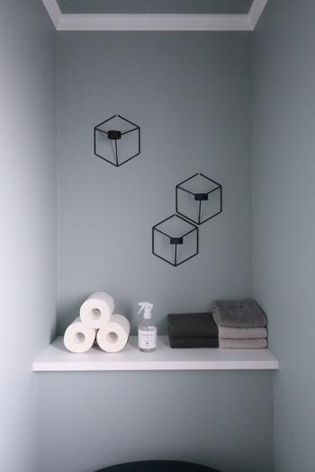 トイレットペーパーの並べ方も工夫次第でおしゃれに。壁にはキャンドルホルダーを飾って、棚には消臭スプレーやタオルなど必要なものをゆとりを持たせて並べているので使いやすく、とってもおしゃれですね。
