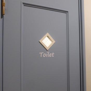 ひし形の窓がおしゃれなドア。Toiletの文字が無ければ、トイレとは思わないくらいかわいいデザインです。落ち着いたブルーグレーが素敵ですね。