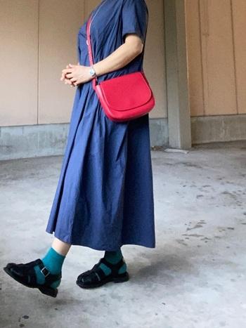 お洒落なブルーのワンピースは、ブルー違いの靴下を合わせて雰囲気をまとめて。バッグでコーデに赤みを入れることで私らしい遊び心を。