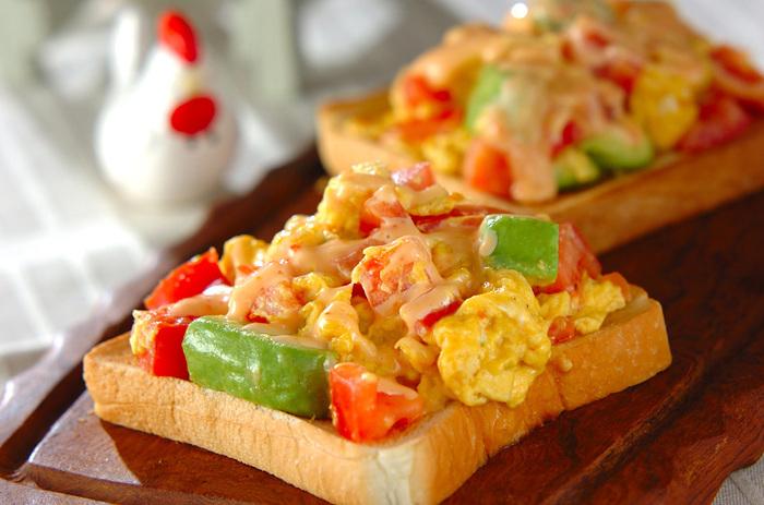 トマトとアボカドがとろっとした卵が絡まったトースト。強火でパパッと仕上げるので、短時間で簡単に作れます◎スイートチリソースとマヨネーズを合わせたソースをかけたらできあがり。トマト・アボカド・卵の彩りがきれいで、大満足のボリュームです。