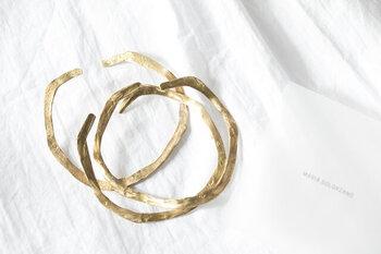 メキシコ出身のコンテンポラリージュエリーデザイナー「MARIA SOLORZANO(マリア ソロザノ)」の個性的なバングル。オーガニックコットンペーパーで型を作り、そこに真鍮を流し込んで作られたので、紙ならではの、やさしい凹凸が生かされています。